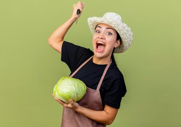 キャベツを保持し、薄緑色の壁の上に立って興奮して叫んでナイフを振るエプロンと帽子の若い美しい女性の庭師