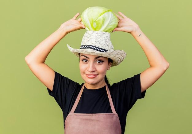 エプロンと帽子をかぶった若い美しい女性の庭師は、薄緑色の壁の上に立って正面を見て笑ってキャベツを頭に抱えています