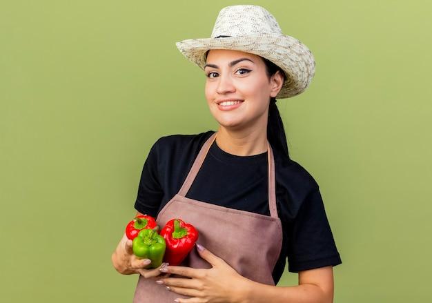 エプロンと帽子をかぶった若い美しい女性の庭師は、明るい緑の壁の上に元気に立って笑顔の正面を見てカラフルなピーマンを保持しています