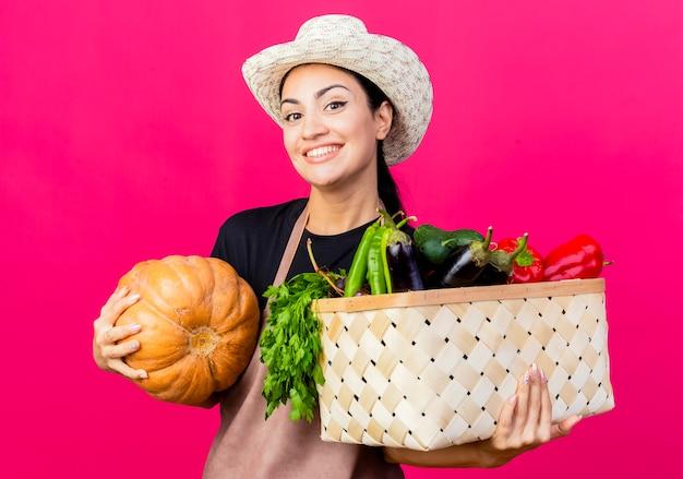 エプロンと帽子の若い美しい女性の庭師は、幸せそうな顔で笑顔の野菜とカボチャでいっぱいの木枠を保持しています
