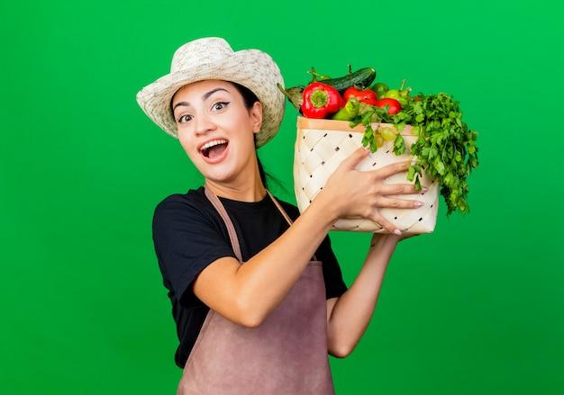 エプロンと帽子をかぶった若い美しい女性の庭師は、緑の壁の上に立っている幸せそうな顔で笑顔で正面を見て野菜でいっぱいの木枠を保持しています