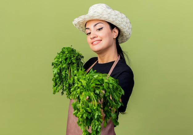 薄緑色の壁の上に元気に立って笑顔の正面を見て新鮮なハーブを保持しているエプロンと帽子の若い美しい女性の庭師
