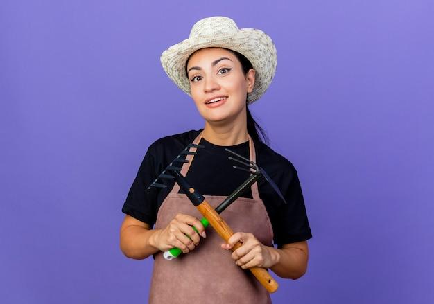 エプロンと帽子をかぶった若い美しい女性の庭師は、青い壁の上に立って自信を持って笑顔の正面を見てガーデニング機器を保持しています
