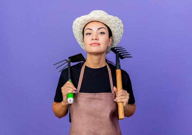 앞치마와 모자 파란색 벽 위에 자신감 서 찾고 원예 장비를 들고 젊은 아름 다운 여자 정원사