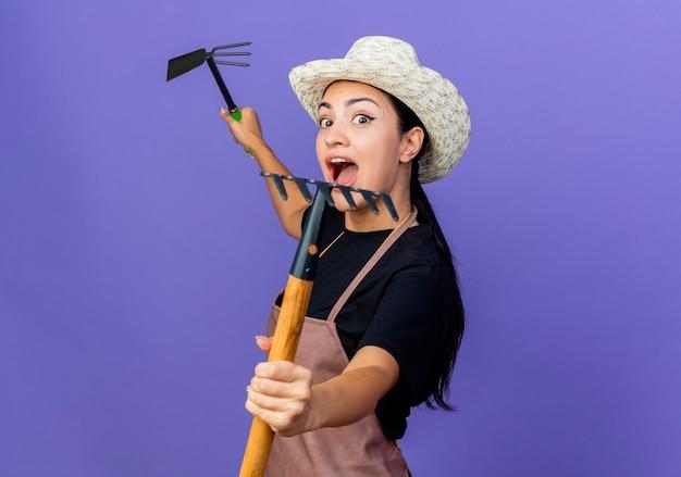 青い壁の上に立って驚いて叫んでガーデニング機器を保持しているエプロンと帽子の若い美しい女性の庭師