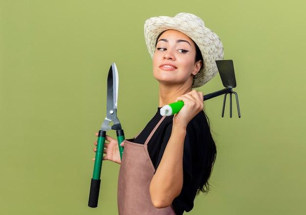 エプロンと帽子をかぶった若い美しい女性の庭師は、薄緑の壁の上に立って笑顔で脇を見てヘッジクリッパーとマットックを保持しています