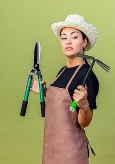 エプロンと帽子をかぶった若い美しい女性の庭師は、薄緑色の壁の上に立っている真面目な顔でそれらを見てヘッジクリッパーとマトックを保持しています