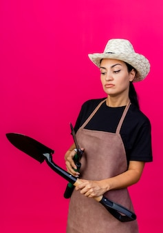 앞치마와 모자를 들고 헤지 가위와 삽에 젊은 아름 다운 여자 정원사 분홍색 벽 위에 서 심각한 얼굴로 옆으로 찾고