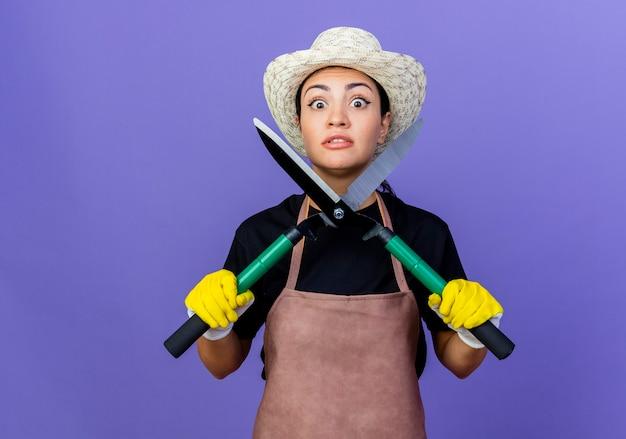 エプロンと帽子をかぶった若い美しい女性の庭師は、青い壁の上に立って混乱し、心配して正面を見てヘッジクリッパーを保持しています