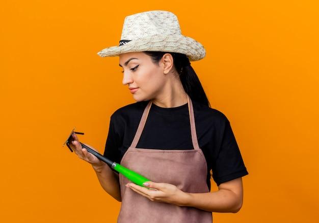 オレンジ色の壁の上に立っている顔に笑顔でそれを見てエプロンと帽子を持った若い美しい女性の庭師