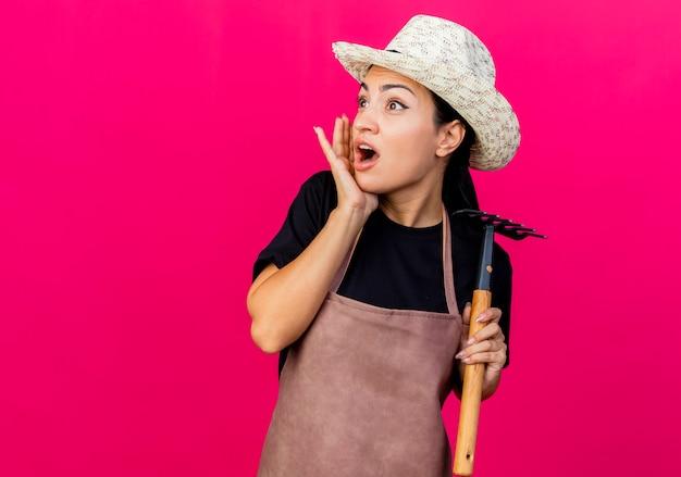 エプロンと帽子をかぶった若い美しい女性の庭師は、ピンクの壁の上に立って驚いて心配して脇を見てミニ熊手を保持しています