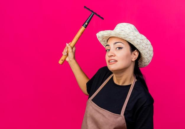 エプロンと帽子をかぶった若い美しい女性の庭師は、ピンクの壁の上に立って混乱して笑って脇を見てミニ熊手を保持しています