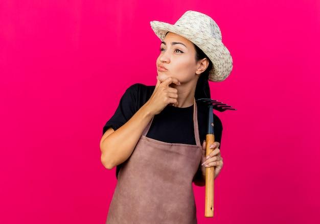 エプロンと帽子をかぶった若い美しい女性の庭師は、ピンクの壁の上に立って物思いにふける表情を考えてあごに手を脇に見ているミニ熊手を保持しています