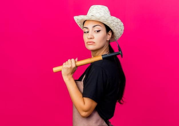 エプロンと帽子をかぶった若い美しい女性の庭師は、ピンクの壁の上に立っている深刻な顔で脇を見てミニ熊手を保持しています