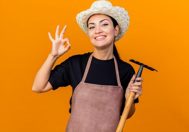 エプロンと帽子をかぶった若い美しい女性の庭師は、オレンジ色の壁の上に立っているokサインを示して笑顔を正面に見てミニ熊手を保持しています