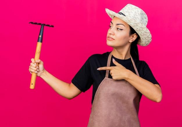 エプロンと帽子をかぶった若い美しい女性の庭師は、ピンクの壁の上に立って自信を持って笑って人差し指でミニ熊手を指しています
