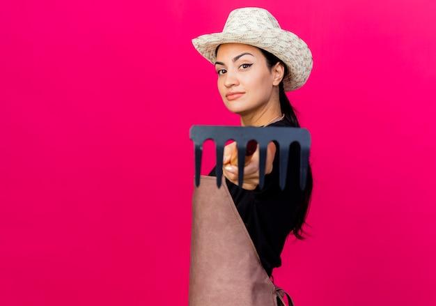 앞치마와 모자에 젊은 아름 다운 여자 정원사 핑크 벽 위에 자신감 서 미소 앞에 그것을 가리키는 미니 갈퀴를 들고