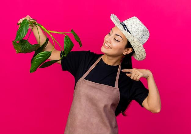 エプロンと帽子をかぶった若い美しい女性の庭師は、ピンクの壁の上に立って微笑んで人差し指で植物を指します