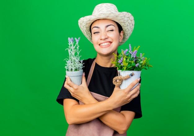 エプロンと帽子をかぶった若い美しい女性の庭師は、緑の壁の上に立って笑顔とウインクを正面から見て鉢植えの植物を保持しています