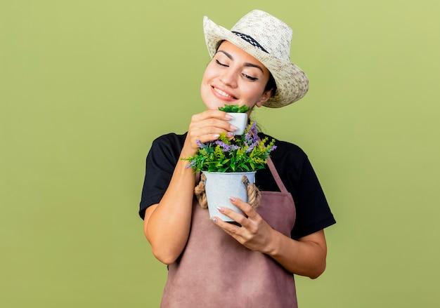 エプロンと帽子をかぶった若い美しい女性の庭師は、薄緑色の壁の上に立っている幸せそうな顔で笑顔でそれを見て鉢植えの植物を保持しています