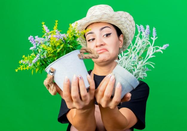 緑の壁の上に立って混乱して不機嫌そうに見える鉢植えの植物を保持しているエプロンと帽子の若い美しい女性の庭師