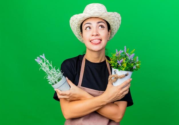 緑の壁の上に立っている舌を突き出て見上げる鉢植えの植物を保持しているエプロンと帽子の若い美しい女性の庭師