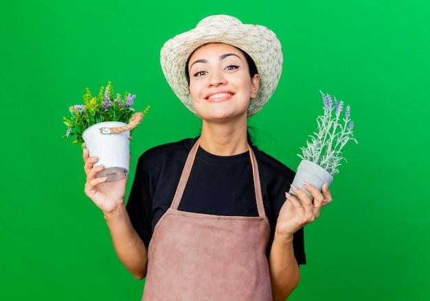 エプロンと帽子の若い美しい女性の庭師は幸せそうな顔で笑って鉢植えの植物を保持しています