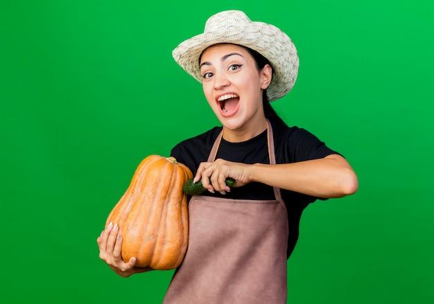 緑の壁の上に立っている幸せな顔で笑顔のカボチャとキュウリを保持しているエプロンと帽子の若い美しい女性の庭師