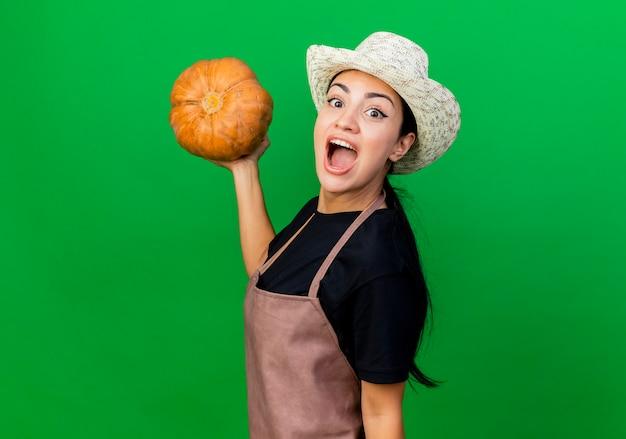 緑の壁の上に立って幸せで興奮して正面を見てカボチャを保持しているエプロンと帽子の若い美しい女性の庭師