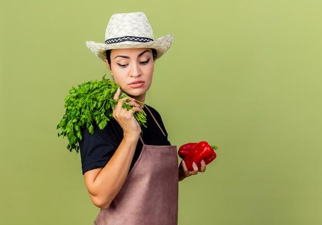 エプロンと帽子をかぶった若い美しい女性の庭師は、薄緑の壁の上に立っている真面目な顔で脇を見て赤いピーマンと新鮮なハーブを保持しています