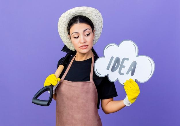 앞치마와 모자에 젊은 아름 다운 여자 정원사 파란색 벽 위에 자신감 서 웃 고 단어 아이디어와 삽과 연설 거품 기호를 들고