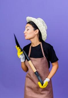 Молодая красивая женщина-садовник в фартуке и шляпе, держащая лопату, собирается поцеловать ее, стоя у синей стены