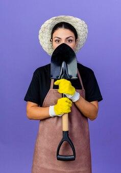 青い壁の上に立ってその後ろに彼女の顔を隠すシャベルを保持しているエプロンと帽子の若い美しい女性の庭師