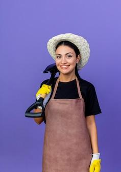 Молодая красивая женщина-садовник в фартуке и шляпе, держа лопату, глядя на фронт, весело улыбаясь, стоя над синей стеной Бесплатные Фотографии