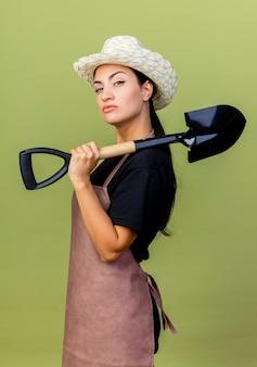 薄緑色の壁の上に立っている真面目な顔で正面を見てシャベルを保持しているエプロンと帽子の若い美しい女性の庭師
