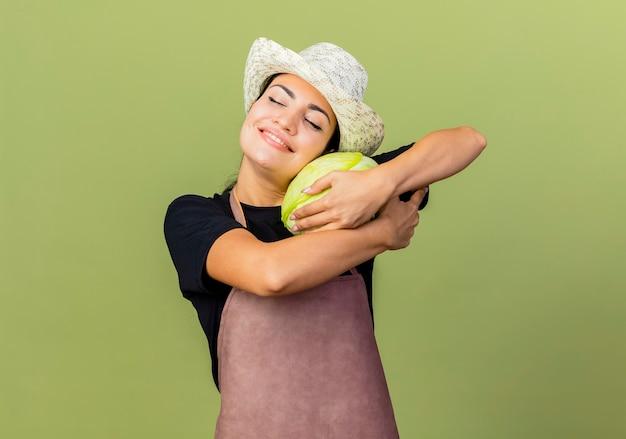 薄緑色の壁の上に立っている目を閉じてキャベツを抱き締めるエプロンと帽子の若い美しい女性の庭師