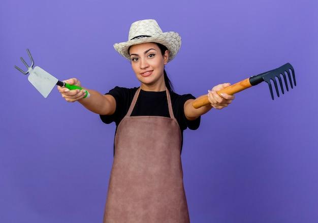 エプロンと帽子をかぶった若い美しい女性の庭師は、青い壁の上に立って笑顔の園芸用品を示しています