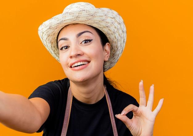 エプロンと帽子の若い美しい女性の庭師は、オレンジ色の壁の上に立って笑顔でokサインを示しています。