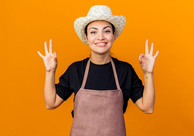 エプロンと帽子をかぶった若い美しい女性の庭師は、オレンジ色の壁の上に立っているokサインを示して笑顔を正面に見ています