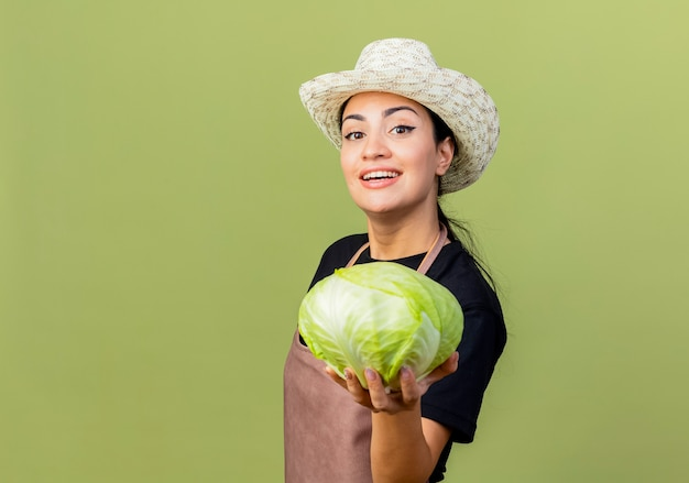 Молодая красивая женщина-садовник в фартуке и шляпе показывает капусту, глядя на фронт, улыбаясь, стоя над светло-зеленой стеной