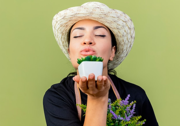 薄緑色の壁の上に立ってキスを吹く鉢植えの植物を示すエプロンと帽子の若い美しい女性の庭師