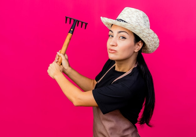 ピンクの壁の上に立って笑顔のエプロンと帽子を振るミニ熊手で若い美しい女性の庭師