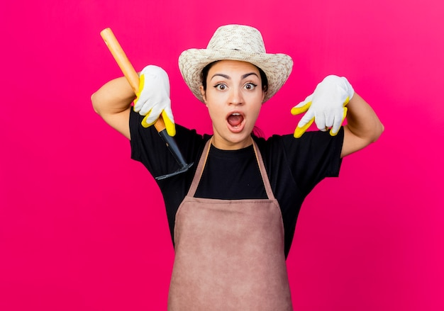 ゴム手袋のエプロンと人差し指を下に向けてミニ熊手を保持している帽子の若い美しい女性の庭師は驚いています