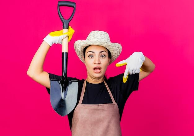 ゴム手袋のエプロンと人差し指を下に向けてシャベルを持って帽子をかぶった若い美しい女性の庭師は驚いています