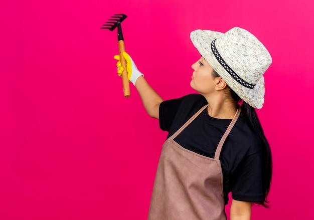 ピンクの壁の上に立っている真面目な顔でそれを見ているミニ熊手を示すゴム手袋エプロンと帽子の若い美しい女性の庭師