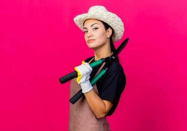 Giardiniere di giovane bella donna in guanti di gomma grembiule e cappello che tiene tagliasiepi guardando davanti con faccia seria in piedi sopra il muro rosa