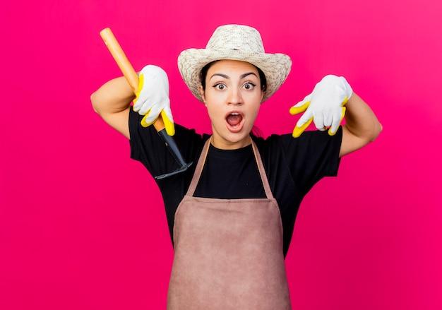 Giardiniere di giovane bella donna in guanti di gomma grembiule e cappello che tiene mini rastrello che punta con le dita indice verso il basso essendo sorpreso
