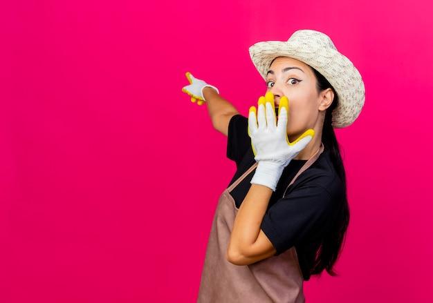 Giardiniere di giovane bella donna in grembiule di guanti di gomma e cappello che punta a qualcosa con il dito indice che è sorpreso in piedi sopra il muro rosa