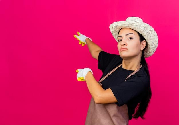 Giardiniere di giovane bella donna in guanti di gomma grembiule e cappello che punta con il dito indice indietro guardando con faccia seria in piedi sopra la parete rosa