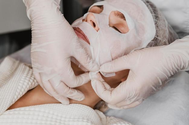 스파에서 피부 마스크 치료를 받고 젊은 아름 다운 여자